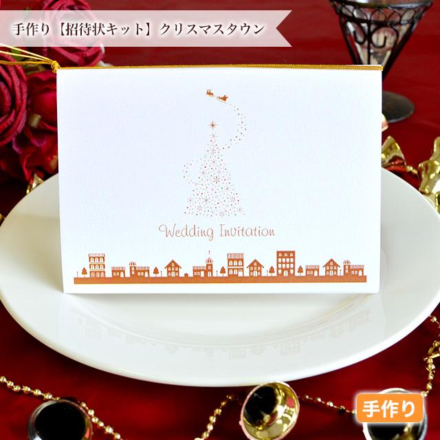 そりに乗ったサンタクロースとキラキラのクリスマスツリー、シルエットの街並みがおしゃれな手作りの招待状